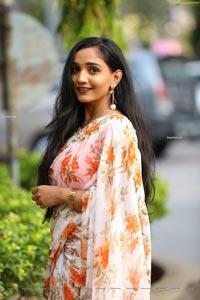 Sruthi in White-Orange Floral Print Saree